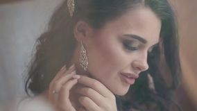 Bride puts on earring. Beautiful bride puts on earring getting ready for wedding stock video footage