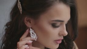 Bride puts on earring. Beautiful bride puts on earring getting ready for wedding stock footage
