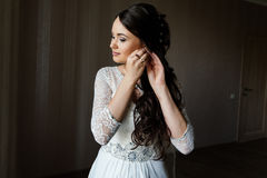 Bride puts on an earring Royalty Free Stock Photos