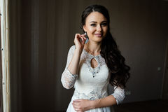 Bride puts on an earring Stock Photos