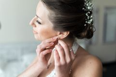 Bride puts on earrings Royalty Free Stock Photography