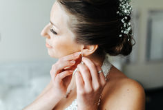 Bride puts on earrings Royalty Free Stock Image