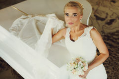 Bride puts her veil on a piano while sitting at it Royalty Free Stock Photography