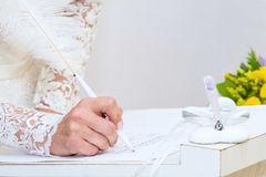 Bride puts his signature. Pen in the registration book of the wedding Stock Photo