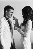 Bride puts a lily on fiance's jacket Royalty Free Stock Images