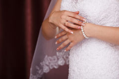 Bride puts on pearl bracelet. Royalty Free Stock Images