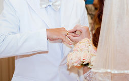 Bride puts the ring on the bridegroom's finger Stock Photo