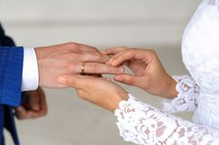 The hands of the bride and groom. The bride puts the ring on the finger of the groom Royalty Free Stock Images
