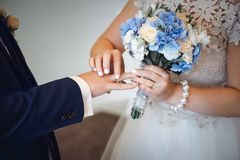 Bride puts ring on groom. The bride puts the ring on the groom and holds flowers Stock Image