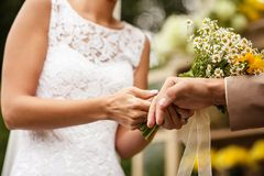 Bride puts ring on groom's finger Royalty Free Stock Photography