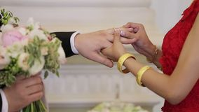 Bride puts a ring to grooms hand stock video