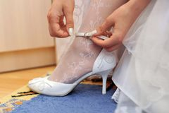 Bride puts on shoe Royalty Free Stock Image