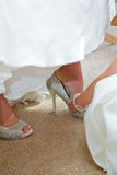 Bride puts on shoes. A bride puts on her high heeled shoes as she gets dressed for her wedding with help from a bridesmaid Royalty Free Stock Images