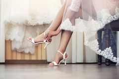 The bride puts on shoes  feet Royalty Free Stock Photography