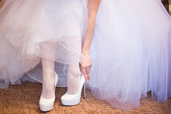 Bride puts on shoes Royalty Free Stock Photo