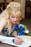 Bride puts signature on registration of marriage Royalty Free Stock Photos
