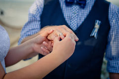 The bride puts on a wedding ring the groom's finger. Sea style wedding Stock Photography