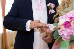 Bride puts wedding ring on grooms finger. Bride and groom exchange rings in wedding day. Wedding ceremony process. Marriage engagement. Exchanging of rings royalty free stock photos