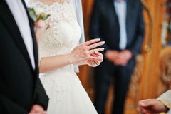 Bride puts wedding ring at hand on church. Stock Images