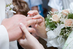 Putting on a wedding ring Stock Images