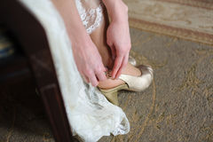 Bride puts on white shoes for wedding Stock Photography