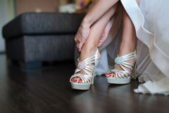 Bride puts on white shoes for wedding Stock Image