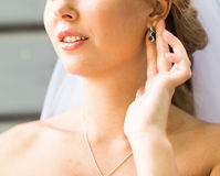 Bride putting on diamond earrings Royalty Free Stock Images