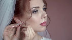 Bride is putting on earrings, close-up, slow motion. Bride is putting on earrings, closeup, slow motion stock video footage