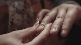 Bride is putting an engagement ring on the finger of the groom during the wedding ceremony, close-up, slow motion. Bride is putting engagement ring on the finger stock video