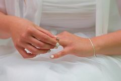 Bride putting engagement ring on wedding day.  Royalty Free Stock Image