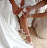 Bride Putting On Gartar. Detail of bridesmaid helping bride put on gartar Stock Photo