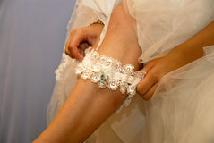 Bride Putting On Garter. Closeup of a bride's leg from ankle to knee, as she pulls the garter up her leg at shin Royalty Free Stock Photography