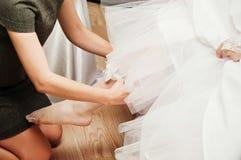 Bride putting garter Stock Images