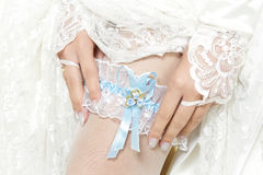 Bride putting a garter with blue ribbon. On her leg. Close up Royalty Free Stock Photos