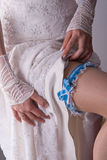 Bride putting a garter with blue ribbon Stock Images