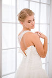 Bride putting on her white wedding dress Royalty Free Stock Images