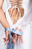 Bride putting on her white wedding dress, closeup bride's hands are linked male tie Royalty Free Stock Photo