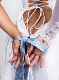 Bride putting on her white wedding dress, closeup bride's hands are linked male tie Stock Images