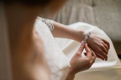 Bride putting on luxury bracelet on hand in the morning, getting ready. royalty free stock photography