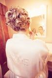Bride putting on makeup. Vintage portrait of a bride putting on makeup in a vanity mirror stock photos