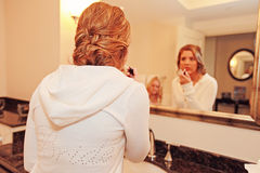 Bride putting on makeup. In a bathroom mirror royalty free stock photo