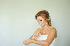 Bride Putting Perfume on Hands. Smiling bride putting perfume on hands Stock Image