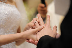 Bride putting a ring on groom's finger Stock Images