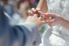 Bride putting a ring on groom's finger Royalty Free Stock Images