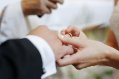 Bride putting a ring on groom's finger Stock Photo