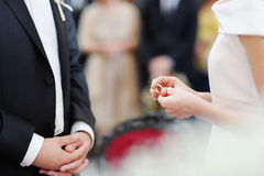 Bride putting a ring on groom's finger stock photography
