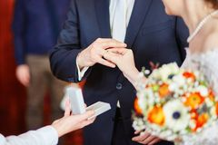 Bride putting the ring on groom's finger Stock Photo