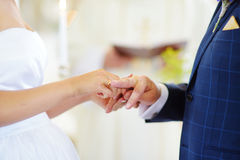 Bride putting a ring on groom's finger Royalty Free Stock Photos