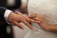 Bride putting ring on grooms finger Royalty Free Stock Photos