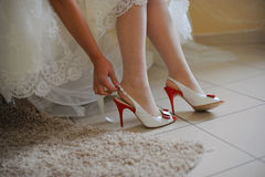 Bride putting on shoes Stock Images